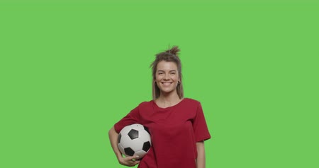 bounce : Funny pretty girl with soccer ball in her hands smilling , appearing ready to play. 4k footage shot on chroma key green background. Stock Footage