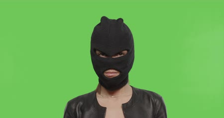 bandido : Close-up of woman in balaclava - crime and violence on green background . Naughty girl in burgal mask having fun . Chroma Key. 4k raw video footage slow motion 60 fps