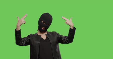 хулиган : sexy woman in balaclava - crime and violence on green background . Naughty girl in burgal mask having fun . Chroma Key. 4k raw video footage slow motion 60 fps