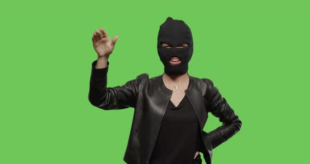 feminism : sexy woman in balaclava - crime and violence on green background . Naughty girl in burgal mask having fun . Chroma Key. 4k raw video footage slow motion 60 fps