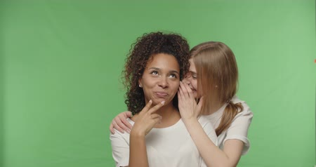 whispering : Two women gossiping, teenage girl sharing secret information with shocked surprised friend, whispering to ear, Female having fun on a Green Screen croma key, 4k raw video footage slow motion 60 fps