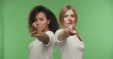 pistol : two attractive girls making gesture sign gun on chroma key background . Happy women having fun on a Green Screen, Croma key, 4k raw video footage slow motion 60 fps Stock Footage