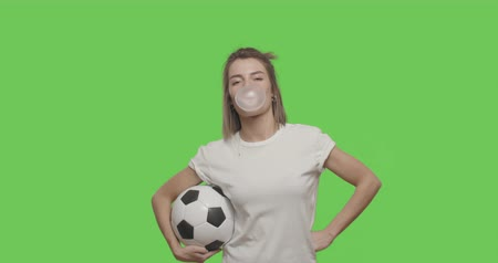 bounce : Funny pretty girl having fun with soccer ball in her hands, blowing bubble chewing gum. 4k footage shot on chroma key green background. Stock Footage