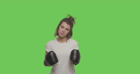 bokser : Caucasian female looking at camera. Sporty girl training fighting, boxing, exercising for self-defense over Green Screen, Chroma Key. 4k raw video footage slow motion 60 fps
