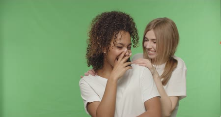 whispering : Two women gossiping, teenage girl sharing secret information with shocked surprised friend, whispering to ear, Female having fun on Green Screen croma key, 4k raw video footage slow motion 60 fps Stock Footage
