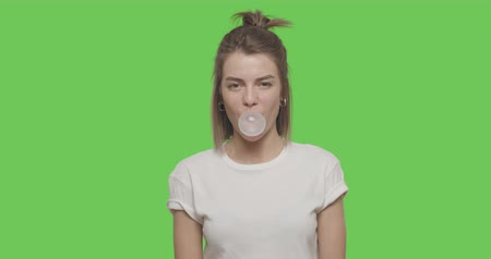 goma : Young girl wear white t-shirt chewing bubble gum over green screen background, Chroma Key 4k raw video footage slow motion 60 fps