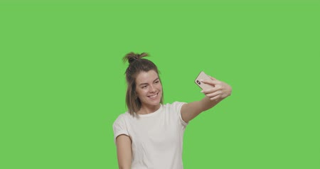looks at the camera : Happy young girl taking selfie photos or self portraits with mobile phone. over green screen background, chroma Key 4k raw video footage slow motion 60 fps Stock Footage