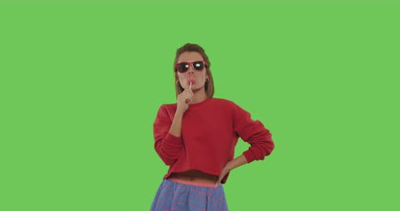 chique : close-up of young tanned emotional woman with big red lollipop over green screen background. Cheerful sexy girl sucking tasty candy on chroma key. 4k raw video footage slow motion