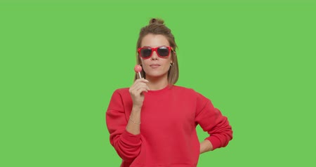 леденец : close-up of young tanned emotional woman with big red lollipop over green screen background. Cheerful sexy girl sucking tasty candy on chroma key. 4k raw video footage slow motion
