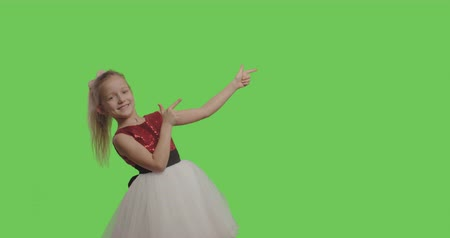 minor : Kid wearing ball dress like princess pointing to side and upwards showing object in copy space over green screen background. Girl having fun on Chroma Key. 4k raw video footage slow motion 60 fps Stock Footage
