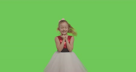 crossed : Young worried child standing with fingers crossed for good luck and wins isolated over Green Screen background . Surprised girl laughing on Chroma Key. 4k raw video footage slow motion 60 fps