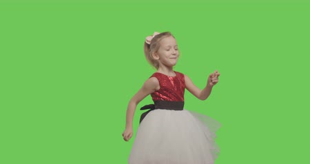 menores : Happy young girl dancing and smiling over green screen background. Happy smiling wearing ball dress like princess on Green Screen, Chroma Key. 4k video footage slow motion 60 fps