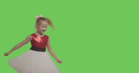 minor : Happy young girl dancing and smiling over green screen background. Happy smiling wearing ball dress like princess on Green Screen, Chroma Key. 4k video footage slow motion 60 fps