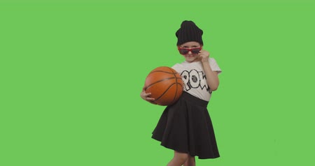 hiphop : young beautiful girl dancing hip hop, street dance over green screen background. Child holding basketball ball on Chroma Key. 4k video footage slow motion 60 fps