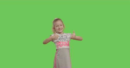 bueno : Young cheerful caucasian child in sunglasses showing like sign over green screen background . Girl making thumbs up on chroma Key. 4k video footage slow motion 60 fps
