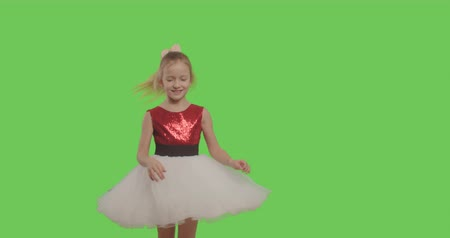minor : Happy young girl dancing and smiling over green screen background. Young cheerful caucasian child showing thumbs up on Chroma Key. 4k raw video footage slow motion 60 fps