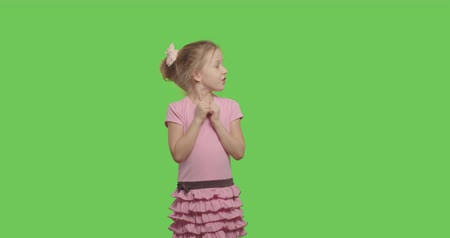 minor : Kid pointing to side and upwards showing object in copy space over green screen background. Child having fun on Chroma Key. 4k raw video footage slow motion 60 fps