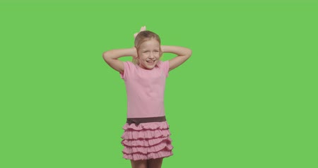 grimacing : Girl closes her ears with her hands isolated on Green Screen, Emotional ghild on chroma Key. 4k raw video footage slow motion 60 fps
