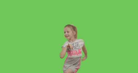 minor : Happy young girl dancing and smiling over green screen background. Happy smiling child on Green Screen, Chroma Key. 4k video footage slow motion 60 fps