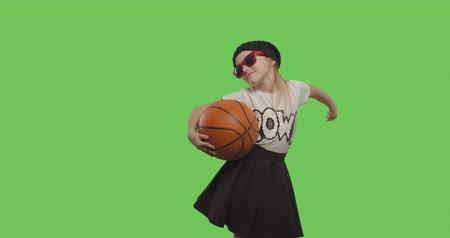 basketball : young beautiful girl dancing hip hop, street dance over green screen background. Child holding basketball ball on Chroma Key. 4k video footage slow motion 60 fps