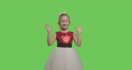 hóquei : Friendly girl waving hand smiling greeting welcoming over green screen background. Cheerful pretty female kid wearing ball dress on chroma key. 4k raw video footage slow motion