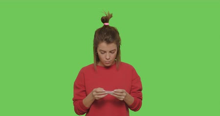 palacz : Young sexy female model rolling cannabis joint over green screen background . Pretty girl smoking marijuana addiction on chroma key. 4k raw video footage slow motion Wideo