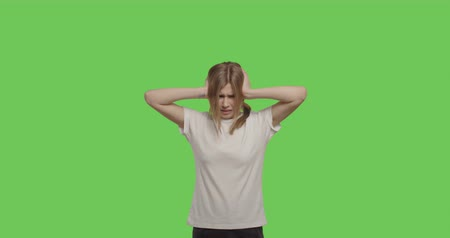 dor de cabeça : young woman puts her hands in her hair and shows a painedisolated over green background, stressed expression. Girl close ears on chroma key . 4k raw video footage slow motion 60 fps