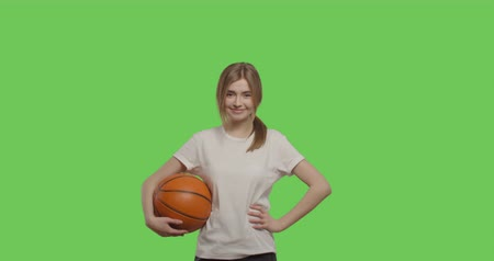 streetball : Girl wearing white t-shirt posing over green screen background. Young woman holding basketball ball on Chroma Key. 4k raw video footage slow motion 60 fps