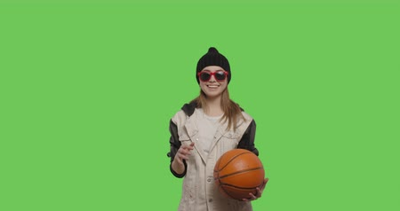 streetball : Girl wearing street hip hop style posing over green screen background. Young woman holding basketball ball on Chroma Key. 4k raw video footage slow motion 60 fps Stock Footage