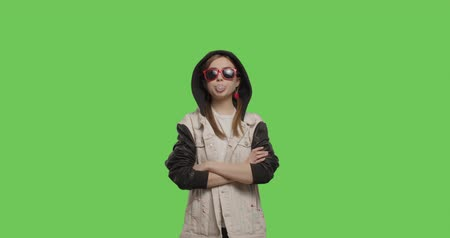 explodindo : Young pretty girl wearing jacket hoodie chewing bubble gum over green screen background, Woman in suglasses having fun on chroma Key . 4k raw video footage slow motion 60 fps