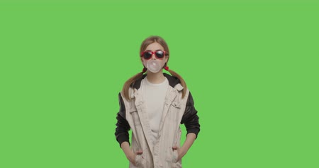 warkocz : Young pretty girl wearing jacket chewing bubble gum over green screen background, Woman in suglasses having fun on chroma Key . 4k raw video footage slow motion 60 fps Wideo