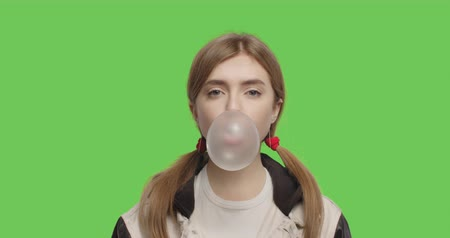 goma : Close-up of face of girl wearing jacket chewing bubble gum over green screen background, Young woman looking at camera on chroma Key . 4k raw video footage slow motion 60 fps
