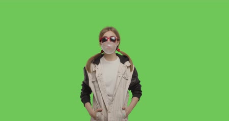 жевать : Young pretty girl wearing jacket chewing bubble gum over green screen background, Woman in suglasses having fun on chroma Key . 4k raw video footage slow motion 60 fps Стоковые видеозаписи
