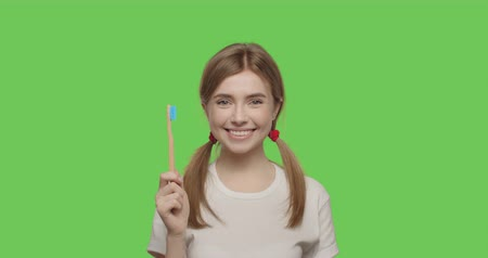 Woman smiling and showing her teeth over green screen background. Girl demonstrating bamboo eco-friendly toothbrush made of wood on chroma key. Zero waste concept. 4k raw video footage slow motion