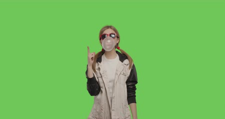 Young pretty girl wearing jacket chewing bubble gum over green screen background, Woman in suglasses having fun on chroma Key . 4k raw video footage slow motion 60 fps Stock mozgókép
