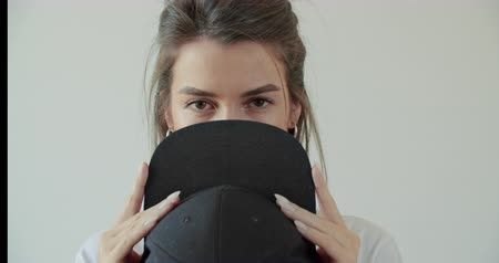 рэп : Hipster girl posing over withe wall. Street swag style, cap, beauty model face. Young woman cover her face black hat. 4k raw footage slow motion