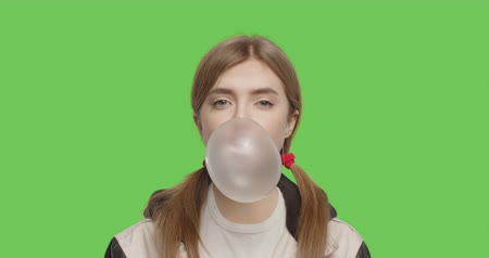 Close-up of face of girl wearing jacket chewing bubble gum over green screen background, Young woman looking at camera on chroma Key . 4k raw video footage slow motion 60 fps