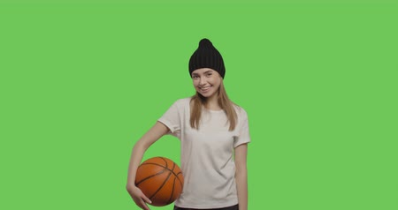 streetball : Girl wearing white t-shirt and black beanie posing over green screen background. Young woman holding basketball ball on Chroma Key. 4k raw video footage slow motion 60 fps
