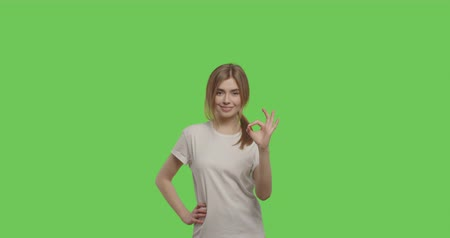 white shirt : Young cheerful caucasian woman showing ok sign over green screen background Chroma Key. 4k video footage slow motion 60 fps