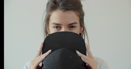 rapper : Hipster girl posing over withe wall. Street swag style, cap, beauty model face. Young woman cover her face black hat. 4k raw footage slow motion