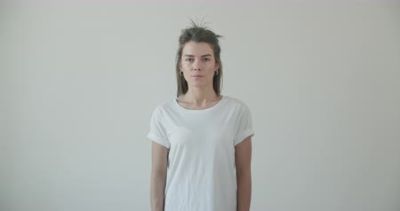 mock : Beautiful young slim girl posing in front of the camera in white blank t-shirt, showing the front for the mock-up. 4k raw footage slow motion Stock Footage