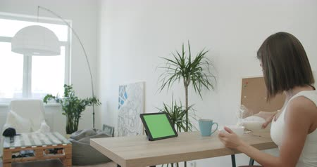 muesli : Attractive woman using her tablet with green screen while having breakfast. Freelance female model girl working out of office. Cup of milk with granola or corn flakes . 4k raw footage slow motion Stock Footage