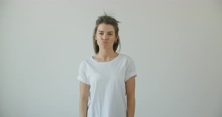 Beautiful young slim girl posing in front of the camera in white blank t-shirt, showing the front for the mock-up, fooling happily. 4k raw footage slow motion