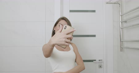 Beautiful caucasian woman taking selfie in mirror in bathroom. Girl having fun. 4k raw footage slow motion