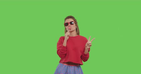 Young woman in sunglasses with big red lollipop over green screen background. Cheerful sexy girl sucking tasty candy on chroma key. 4k raw video footage slow motion