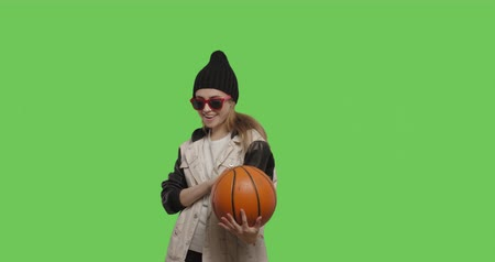 Girl wearing street hip hop style posing over green screen background. Young woman holding basketball ball on Chroma Key. 4k raw video footage slow motion 60 fps Stock mozgókép