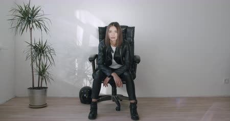 Young motorcyclist woman in black leather jacket woman sits in a chair. Biker girl rests at home. 4k raw slow motion footage Stock Footage