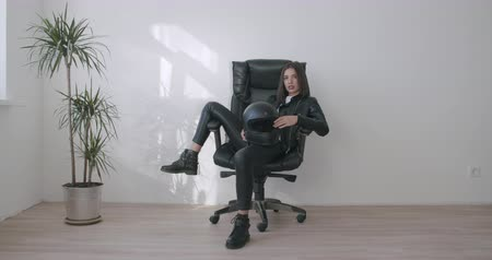 Young motorcyclist woman in black leather jacket woman sits in a chair at home. Biker girl rests and holds fullface motorcycle helmet. 4k raw slow motion footage Stock Footage