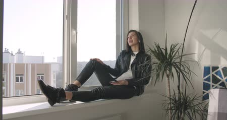 Young woman using mobile phone resting on window sill at home. Motorcyclist girl in black leather jacket holding smartphone. Work out office . 4K raw video footage slow motion