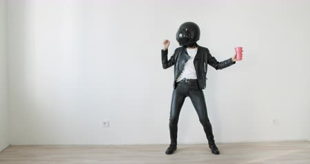 Young woman dance and have fun over white wall background. Biker funny girl in leather jacket and black helmet eat colored popcorn . 4k raw slow motion footage